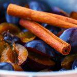 Pflaumen mit Zucker und Gewürzen mischen, etwas Saft ziehen lassen